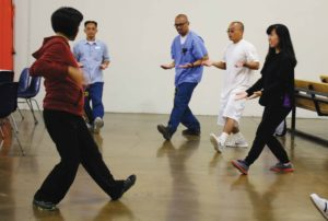 Volunteers and inmates participated in a group Tai Chi exercise
