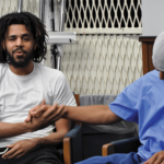 J. Cole at the San Quentin Media Center shaking hands with Miguel Sifuentes