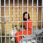 A woman sitting in one of the United States' many jail cells around the country
