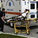 firefighter paramedics loading patient into ambulance