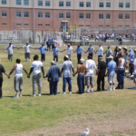 Visitors and inmates making the circle of peace at the Lower Yard