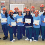 Graduating class of the pre-apprentice program displaying their certificates