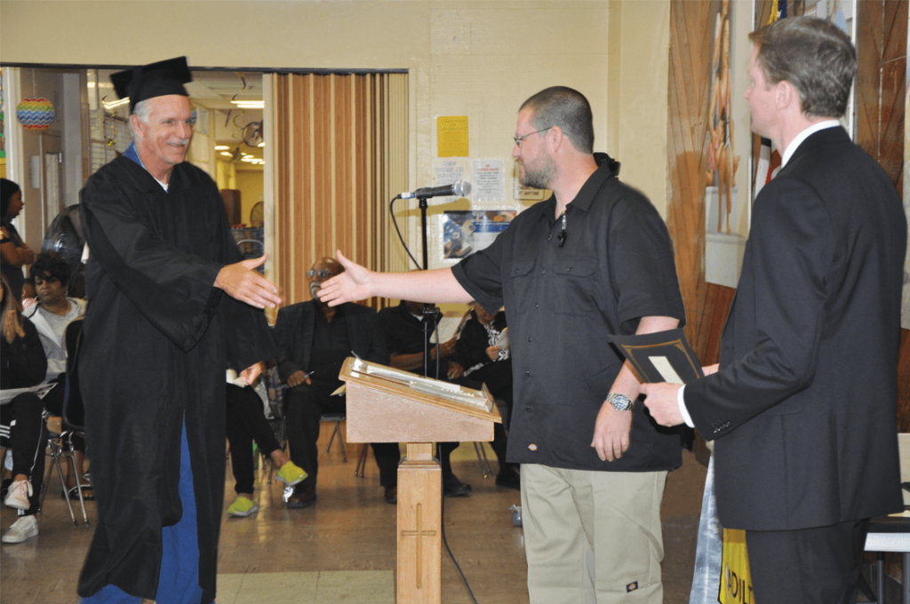 Graduate Thomas Colt to shakes hands with Instructor Leonida and Principal Wheelis