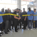 Titan Gilroy cutting the tape of the Titan Machine Shop at San Quentin