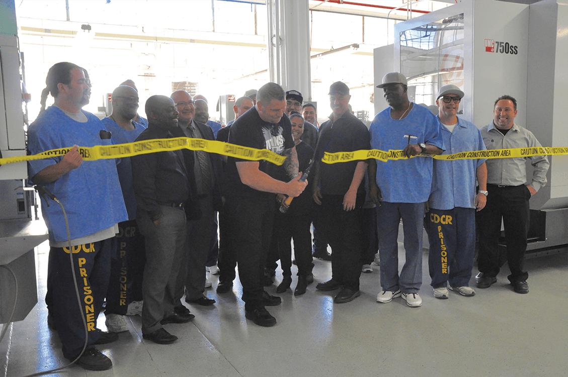 Titan Gilroy cutting the tape of the Titan Machine Shop at San Quentin