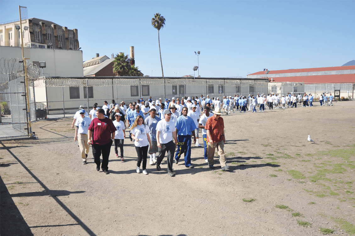 Project Avary sponsors with inmates walking on the Lower Yard