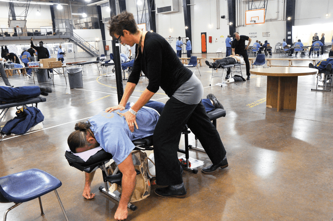 Chiropractor adjusting the back of a participant