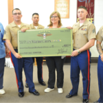 The United States Marines accepting the check from Madeline Tenney