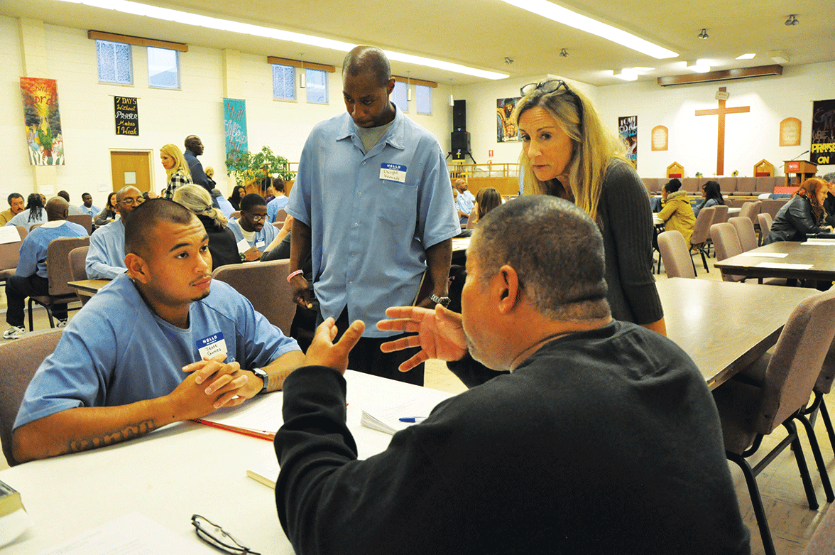 Jesse Gomez speaks with potential employers as Dianna Williams and Dwight Kennedy watch