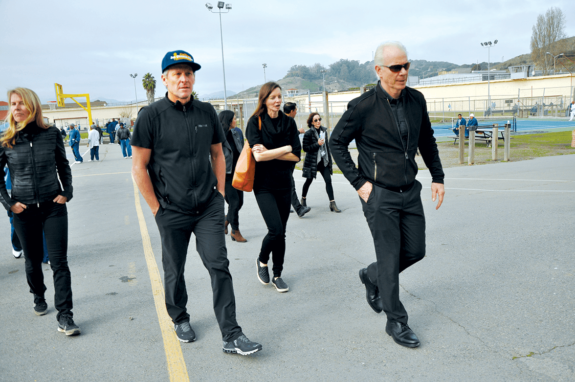 Lance Armstrong and Chris Redlitz walking across San Quentin's Lower Yard