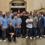 Code.7370 and their instructors posing with Lance Armstrong
