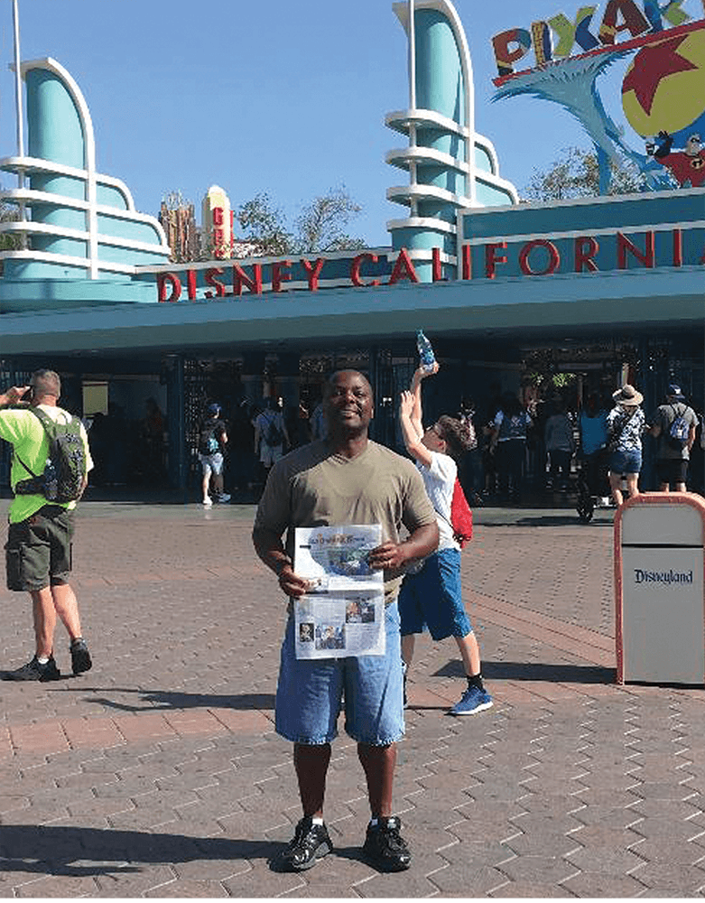 Lt. S. Robinson sharing his SQ News in front of Disneyland, California