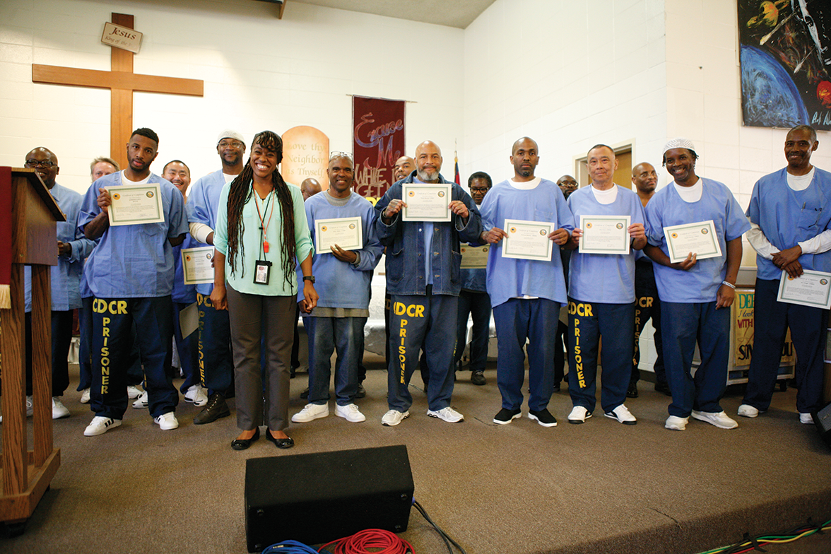 Graduates of Center Point holding up their certificates with Ms. Winston