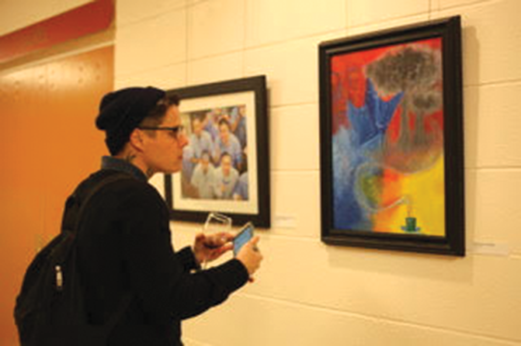 Patron admiring Patrick Maloney's work (right)