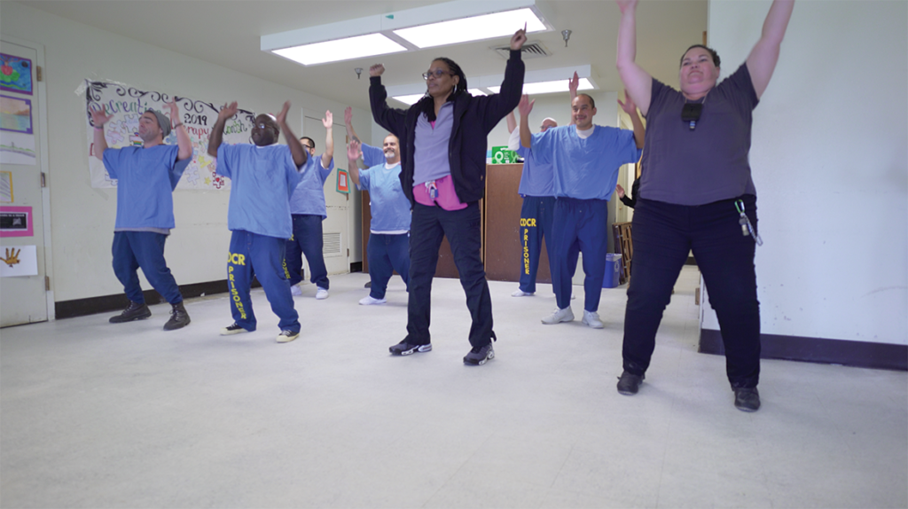 The No Limits Dance Crew with San Quentin staff performing a dance in front of an audience