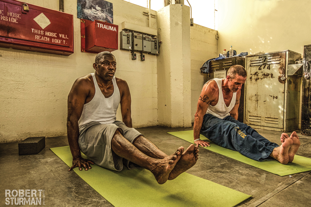 "Darrell ""Moe"" Washington and Daniel Plunkett doing yoga poses in the SQ Education building"