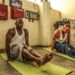 "Darrell ""Moe"" Washington and Daniel Plunkett doing yoga poses in the SQ Education building"