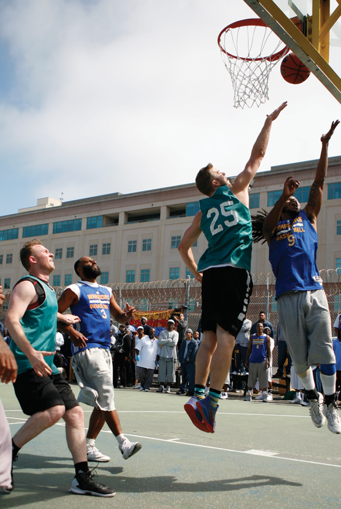 Golden State Warriors Assistant GM Kirk Lacob (green jersey) guarding Jamal Harrison (Warriors #3) on the San Quentin lower yard as Patrick Lacey challenges Delvon Adams