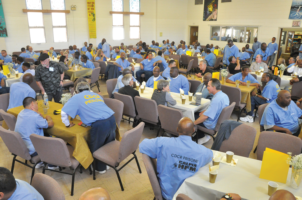 Volunteers & Inmate guest chatting in pre-banquet fellowship as music plays