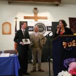Robert E. Burton Principal Michael Wheeless, receiving the Distinguished School award from OCE Superintendent Shannon Swain with Warden Ron Davis (Center)