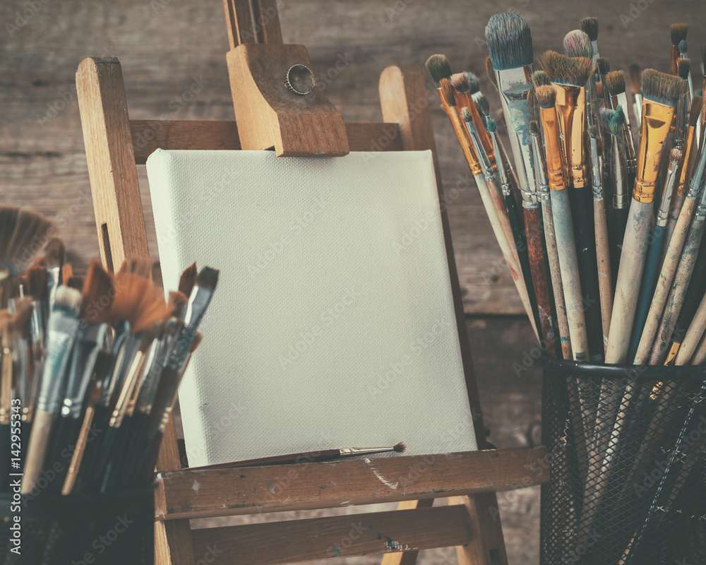 Artistic equipment: empty artist canvas on easel and paint brushes in a artist studio. Retro toned photo.